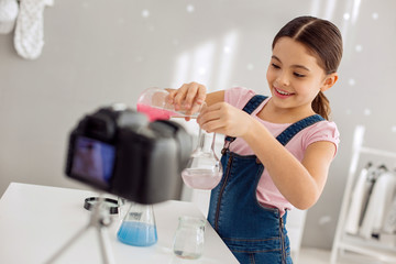 Little prodigy. Adorable pretty pre-teen girl pouring a pink chemical into the flask with water and smiling cheerfully while recording a video blog