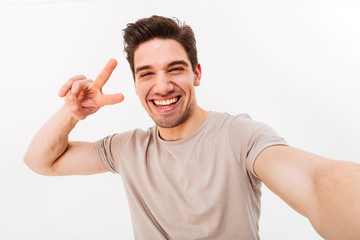 Smiling guy with brown hair showing peace sign on camera while photographing himself, isolated over white background