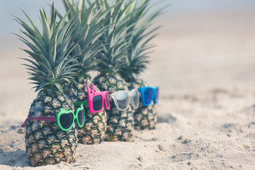Attractive pineapples on the beach Wearing stylish mirrored sunglasses, Tropical summer vacation concept, Sunny day on the beach of tropical island.
