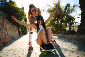 Two female friends playing with skateboard