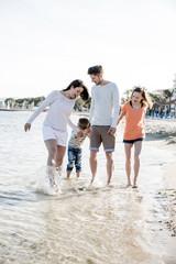 Familie mit 2 Kindern beim Strandspaziergang