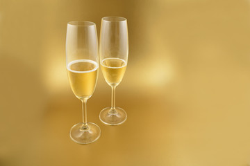 Glass with champagne stock images. Glass with champagne on a golden background. Champagne on a golden background with copy space for text. Festive golden background