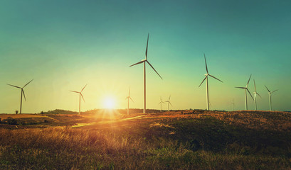 concept idea eco power energy. wind turbine on hill with sunset