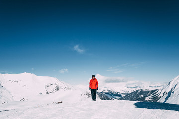 young man smiling at camera while standing in snow-covered mountains in mayrhofen ski area, austria