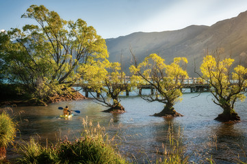 Small canoe in the shallow water at Glenorchy Wharf close to sunset with the trees on Wakatipu lake shore glowing at golden hour