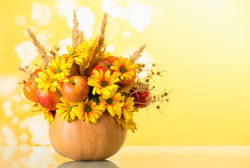 Original bouquet of fruits and flowers in vase of pumpkin, on light yellow