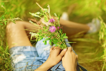 Stylish hipster woman holding bouquet of wildflowers in sunny countryside.  Space for text. Beautiful moment.