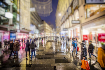 people walking on rainy night streets in vienna