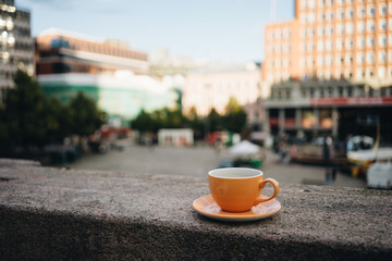 Orange coffee cup in city center