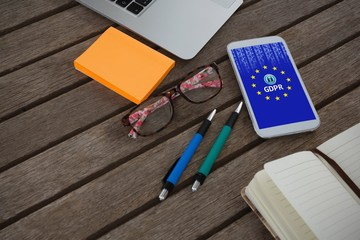 Composite image of mobile phone, laptop, pen, sticky note,