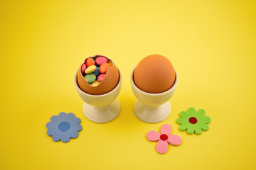 Candy easter eggs stock images. Easter eggs on a yellow background. Spring decoration images. Easter decoration with flowers. Sweet egg with surprise. Egg filled with candy. Easter concept