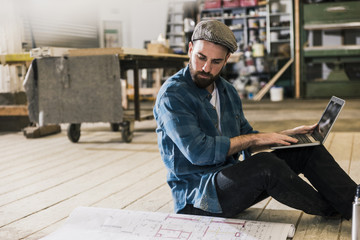 Man with laptop sitting on the floor looking at construction plan