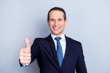 Attractive, executive, corporate, fashionable, modern, positive, executive, corporate politician, economist, financier in formal wear with tie, showing thumbs up front, standing over gray background
