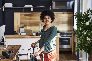 Portrait of smiling young woman with bicycle in modern office