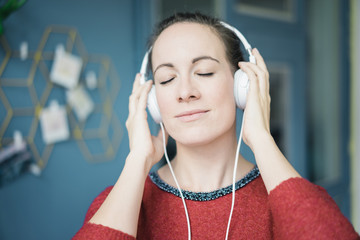 Portrait of woman with eyes closed  listening music with headphones