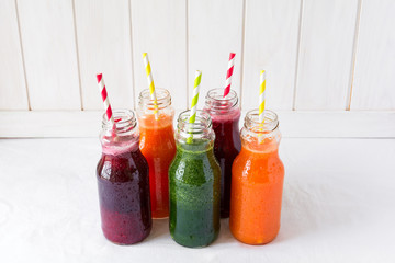 Detox drinks in bottles: fresh smoothies from vegetables: beetroot, carrot, spinach, cucumber and apple on white background