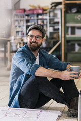 Smiling man with cup of coffee and construction plan sitting on the floor