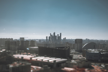 True tilt-shift view from the high point of the cityscape on a sunny day with the city center and the group of business and residential skyscrapers in the background and strong bokeh in the foreground