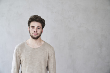 Portrait of confident young man in front of grey wall