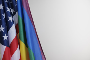 closeup of a gay pride flag and a flag of the United States of America