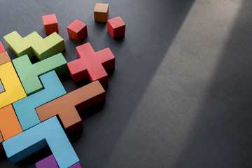 Different colorful shapes wooden blocks on black background, flat lay. Geometric shapes in different colors, top view. Concept of creative, logical thinking or problem solving. Copy space.