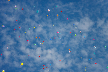 Multicolored balloons flying against the blue sky