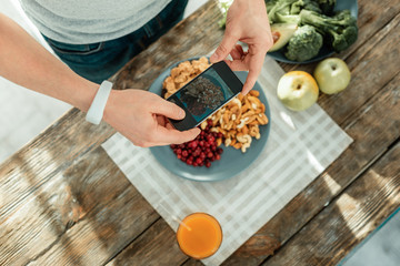 Good photo. Healthy creative concentrated man holding the smartphone in his hands making photo and standing near the table.