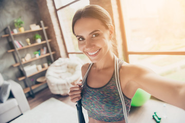 Close up portrait of excited active attractive cheerful beautiful strong skinny with beaming smile wearing sportive top with jump-rope on shoulders taking selfie for social-networks