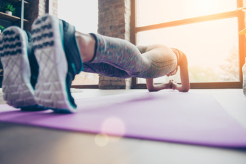 Close up photo of sportswoman's sneakers. Athlete is holding plank position standing on elbows on purple carpet in class club gym view on window with sunlight, sunshine, reflection