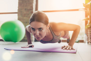 Low-angle close up portrait of beautiful confident will-powered successful sportswoman doing push-ups on the floor purple carpet in sunny day, sun ray, beam, glare