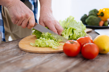 Nutrition source. Young male attractive hands using knife while preparing salad and pressing cabbage again surface
