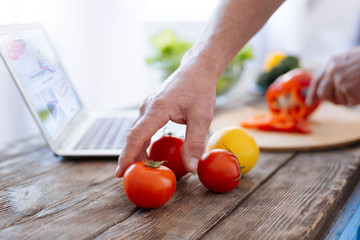 Tools for biohacking. Selective focus of charming strong male hands getting tomato for practicing biohacking diet and preparing lunch