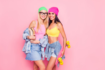 Opposites attract! Cute beautiful fancy funky with toothy smile girls dressed in casual colorful tops, skirts, shorts are embracing and holding book and skateboard, isolated on bright pink background