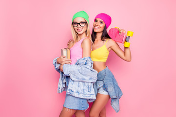 Bright colorful vivid lifestyle! Attractive cheerful smiling joyful women dressed in summer demin shorts, skirt are cuddling holding skate on a shoulder and book in hands, isolated on pink background