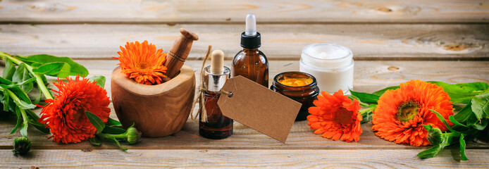 Calendula aromatherapy. Essential oil and cosmetics, blank tag, banner. Wooden table background