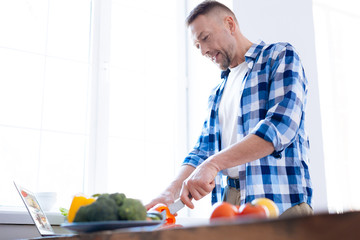 Food is fuel. Pleasant glad focused man holding knife for chopping salad and consuming vegetables
