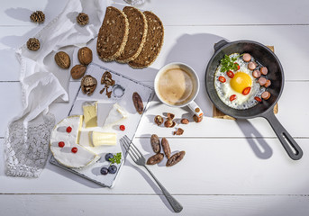 cheese, a cup of coffee and a black cast-iron frying pan with a fried egg