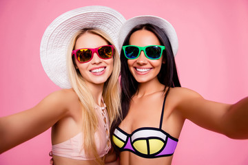 Self portrait of pretty, stylish, hot, cute, trendy tourists, ladies in swimsuits with beaming smiles shooting selfie together on front camera of smart phone, isolated on pink background