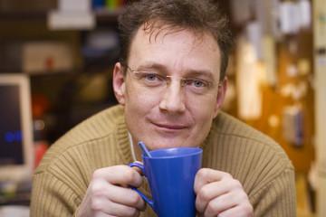 Freundlicher Mann mittleren Alters mit zufriedenem Gesicht und blauer Kaffeetasse in beiden Händen sitzt an seinem Arbeitsplatz und macht Pause