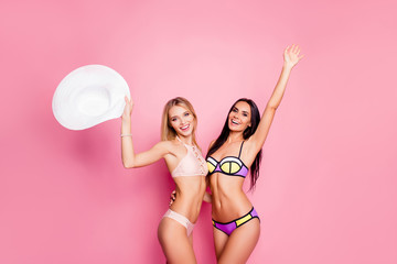 Wall Mural - Pretty, successful, fit, confident, playful, attractive, two girls in swim suits embracing, holding hat with hands up, embracing, having pool party, standing over pink background, women's day