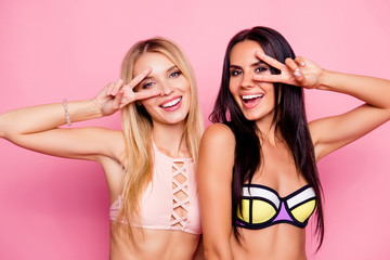 Close up portrait of happy beautiful attractive playful charming cute smiling women wearing swimsuit, are showing v-sign near their eyes, isolated on bright vivid pink background