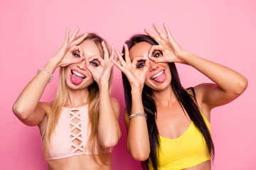 Close up photo of pretty, trendy, nice, creative, blonde, brunette, attractive, charming girls on holidays making binoculars with their fingers and showing tongue standing over pink background