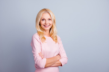 Wellness blonde hair correction skin nourishing people person concept. Portrait of excited cheerful beautiful confident middle-aged woman standing with crossed arms isolated gray background copy-space