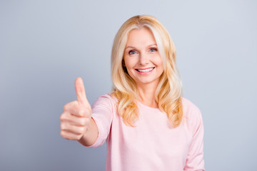 Close up portrait of cheerful glad cute cheerful lovely beautiful attractive confident pretty mature lady making demonstrating thumb-up isolated on gray background selective focus copy-space