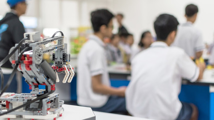 Robotic lab class with school students blur background learning in group having study workshop in science technology engineering classroom for education concept