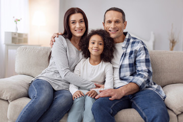 Happy family. Pretty joyful curly-haired girl smiling and sitting on the couch with her parents and they hugging her