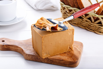 Norwegian brunost on white table. Traditional Scandinavian brown cheese.