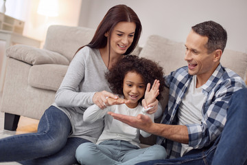 Inspired family. Pretty inspired curly-haired smiling and having fun with her parents while they all sitting on the floor