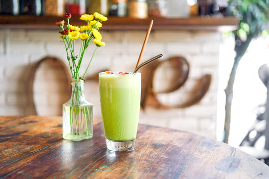Green matcha boba or bobble tea on a wooden table with yellow flowers in a transparent vase. On the back of a blurry background, a white brick with an word - love. Bali restaurant.Side view copy space