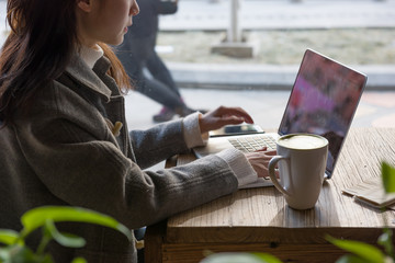 Attractive young woman using laptop in cafe. Matcha Latte, smartphone.
